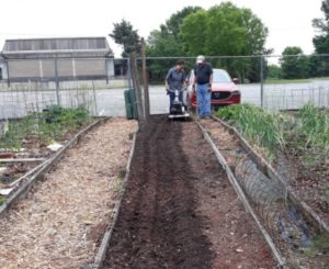 Quina learning to use a new tool in a community garden.